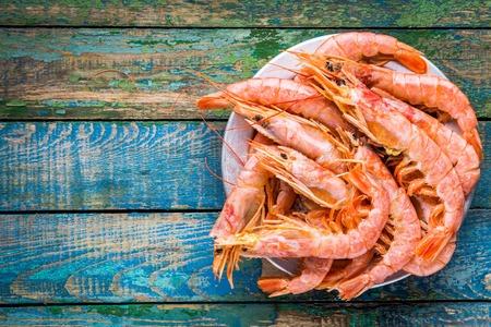 木製のテーブルの上にボウルに新鮮な生海老