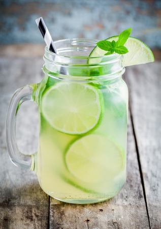 jar: homemade lemonade with lime, mint in a mason jar on a wooden rustic table Stock Photo