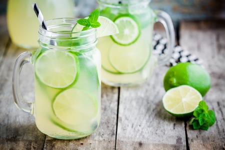 homemade lemonade with lime, mint in a mason jar on a wooden rustic table Archivio Fotografico