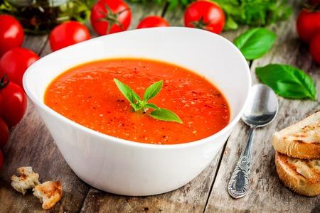homemade vegetarian tomato cream soup in white bowl on wooden table