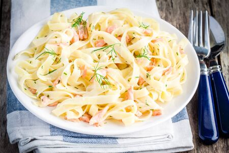 meat sauce: Homemade tagliatelle with salmon and dill on a rustic wooden table