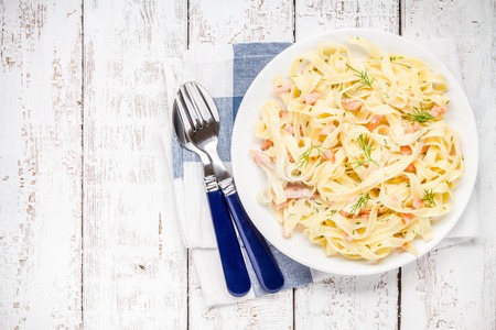meat alternatives: Homemade tagliatelle with salmon and dill on a rustic wooden table top view
