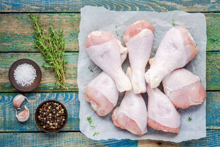 raw organic chicken legs on paper with thyme, salt and pepper on a wooden table Reklamní fotografie
