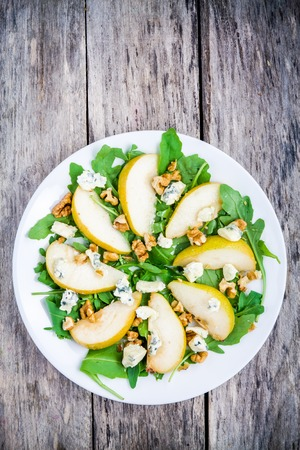 fresh salad with arugula, pear, walnuts and blue cheese on wooden background