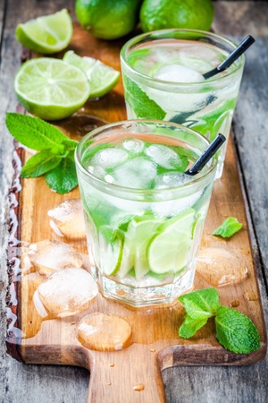 two cold mojitos cocktail on rustic wooden table