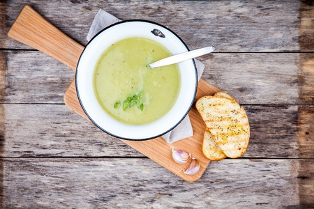 leeks: homemade cream soup with asparagus and toasted ciabatta on rustic background