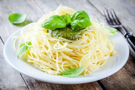 Spaghetti con pesto e basilico su fondo rustico di legno