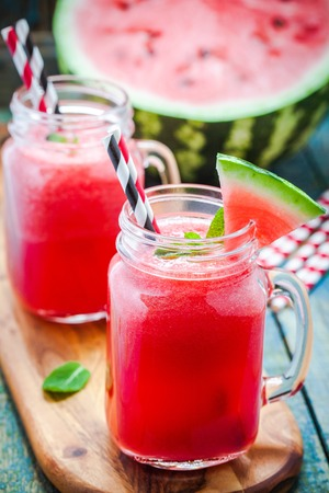 non alcoholic beverage: Watermelon smoothie in a mason jar on a wooden board