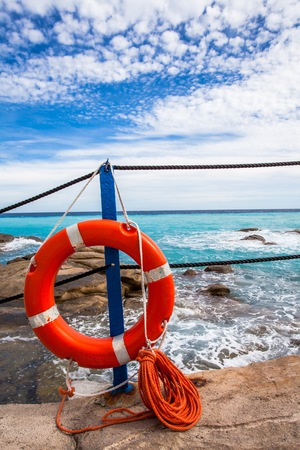 life insurance: Lifebuoy at the beach, turquoise sea, blue sky