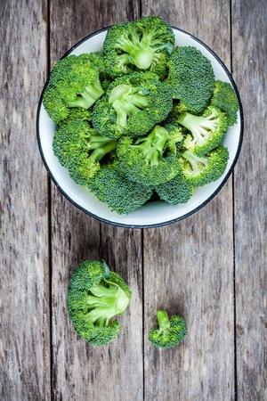 brocoli: Brócoli orgánico sin procesar fresco en un tazón en una vista de fondo de madera superior Foto de archivo