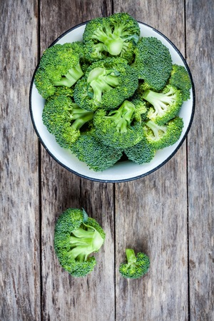 Fresh raw organic broccoli in bowl on a wooden background top view