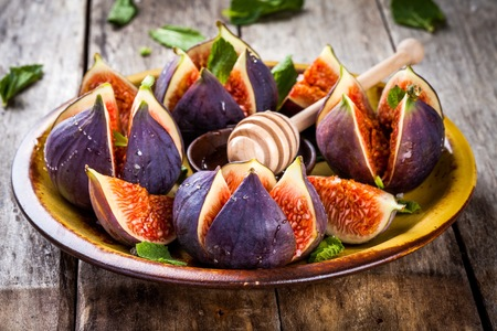 Fresh ripe figs with honey and mint leaves on a rustic wooden table