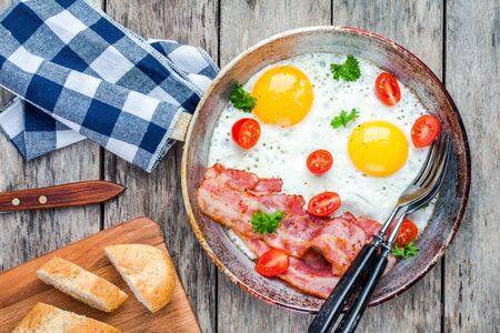 meat and alternatives: Breakfast with fried eggs, bacon, tomatoes and parsley on rustic table Stock Photo