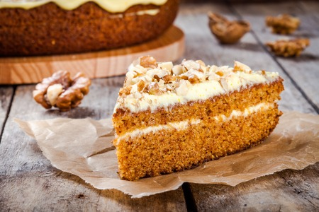 a piece of homemade carrot cake with walnuts on a wooden table. rustic style