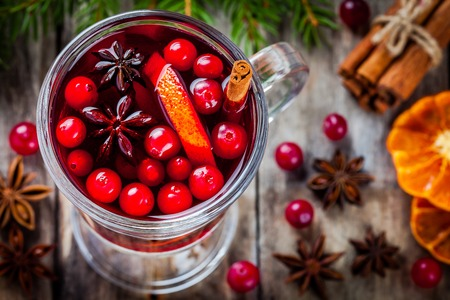 homemade mulled wine with orange slices, cranberries, cinnamon and anise on wooden table Stockfoto