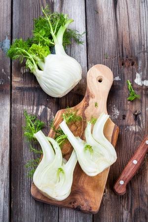 bulb and stem vegetables: Fresh organic fennel on wooden cutting board