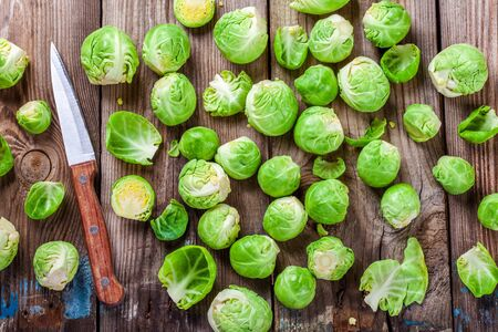 brussels sprouts: Fresh organic Brussels sprouts with knife on a wooden table