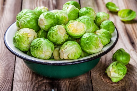 Fresh organic Brussels sprouts in a bowl on a wooden table