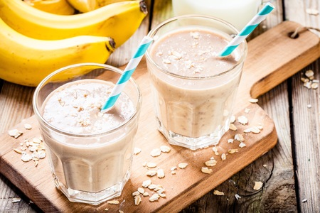 Healthy breakfast: banana smoothie with oatmeal, peanut butter and milk Stock Photo