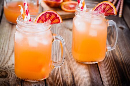 nonalcoholic: non-alcoholic blood orange cocktail in a glass jar on a wooden background