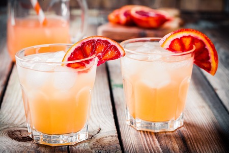 nonalcoholic: nonalcoholic blood orange cocktail in a glass on a wooden background