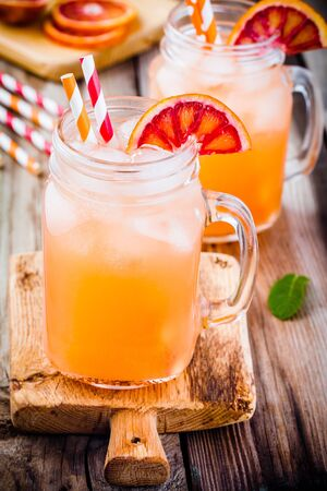 nonalcoholic: nonalcoholic blood orange cocktail in a glass jar on a wooden background Stock Photo