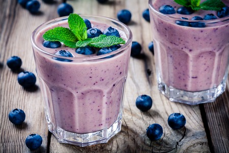 Blueberry smoothie in a glass on a rustic table