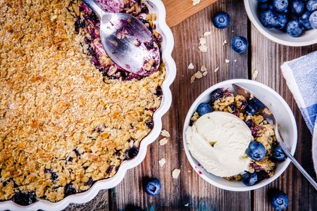 homemade oatmeal blueberry crumble with ice cream on wooden table