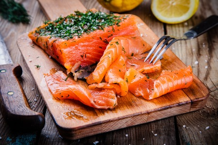 homemade smoked salmon with dill on a wooden table