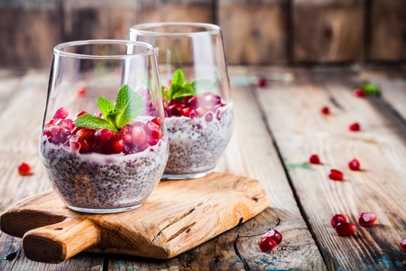 chia pudding with pomegranate seeds and mint on rustic wooden table Reklamní fotografie