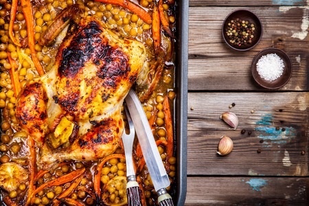 whole chicken: Roasted whole chicken with chickpeas, carrots and lemons. Top view