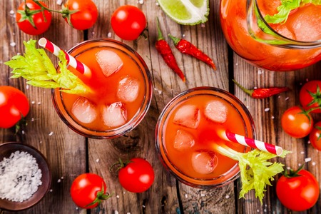 tomato juice with celery and ice in glasses on a wooden table