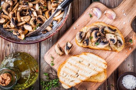 Bruschetta with fried mushrooms on wooden cutting board 스톡 콘텐츠