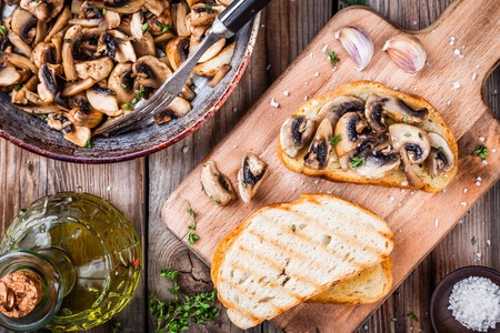 bruschetta: Bruschetta with fried mushrooms on wooden cutting board Stock Photo