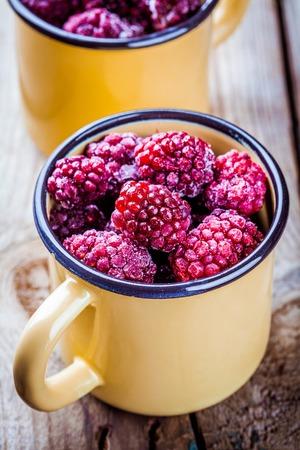 brambleberry: Frozen blackberries in a mugs on a rustic wooden table
