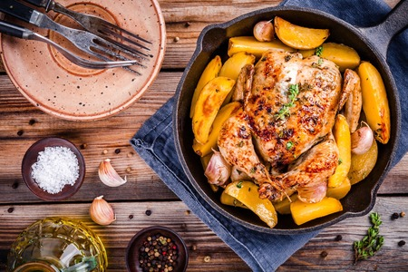 Roasted whole chicken with potatoes and thyme in a cast iron skillet