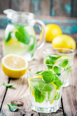 summer iced drink with lemon and mint on wooden rustic table