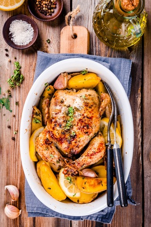 whole chicken: Roasted whole chicken with potatoes and thyme on wooden table