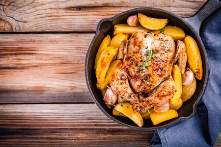 whole chicken: Roasted whole chicken with potatoes and thyme in a cast iron skillet