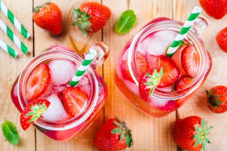 Strawberry lemonade with ice in mason jar on a wooden table