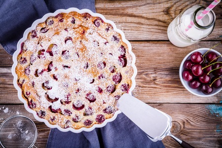 Clafoutis cherry pie on rustic wooden background Stock Photo