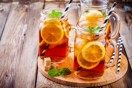 ice tea with slice of lemon in mason jar on the wooden rustic background