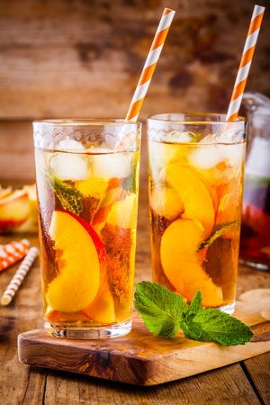 Peach ice tea in a glass with mint on wooden table Reklamní fotografie
