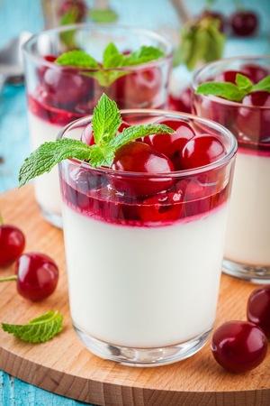 summer pudding: homemade dessert panna cotta with cherry sauce and mint