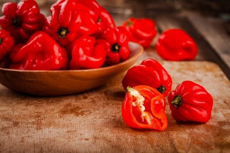 habanero: fresh red hot habanero chili peppers  on wooden background Stock Photo