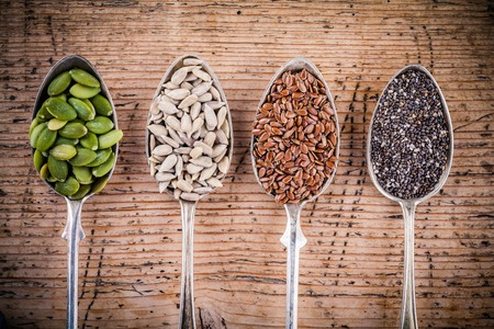 健康的なスーパー フード: カボチャの種、ヒマワリの種、亜麻の種子、木製のテーブルにチア 写真素材