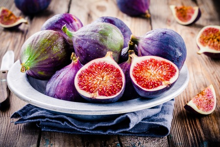 Fresh ripe figs in a bowl closeup on a wooden background