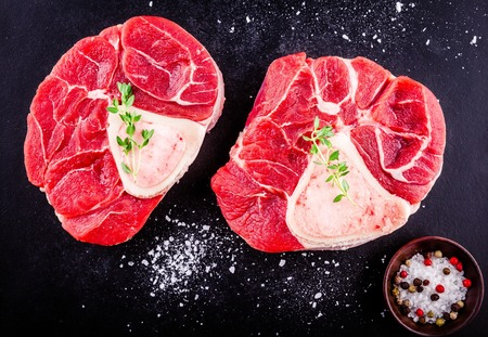 two raw fresh veal shank meat for ossobuco on dark background Standard-Bild