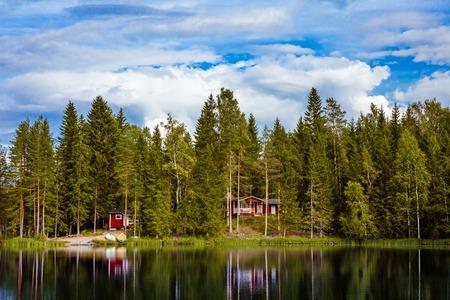 cabaña de madera de color rojo por el lago en Finlandia rural