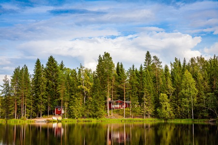 Red wooden cottage by the lake in rural Finland